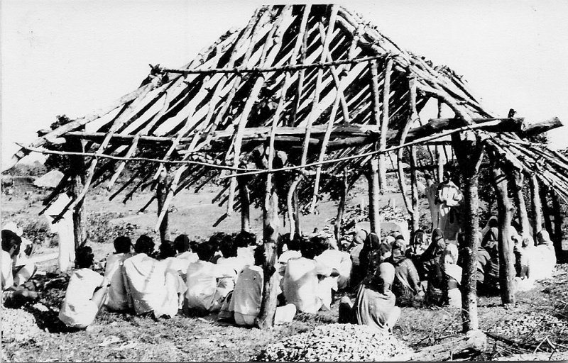 Local people gather in a typical 'prayer hut' which is still under construction. 1975.