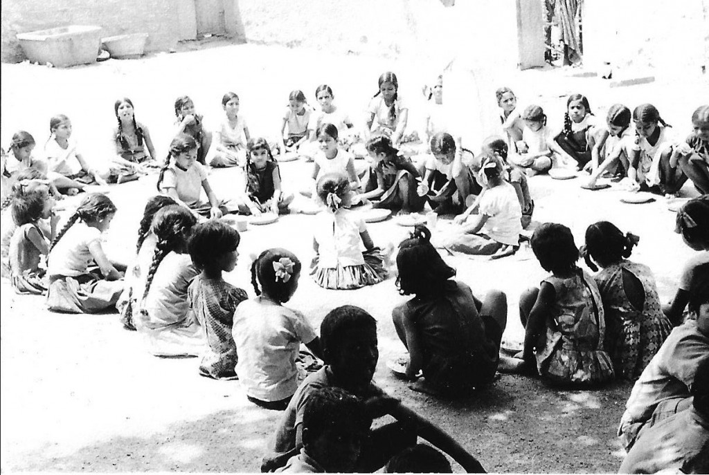 Boarding children having their main meal: rice, curry and dhal on small tin plates.