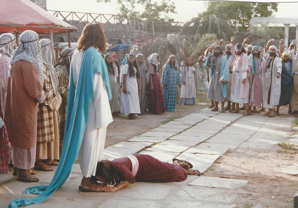The pharisees throw a woman caught in adultery at Jesus' feet